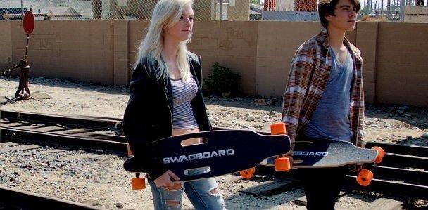 personas llevando longboard electrico