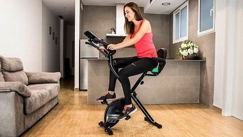 BICICLETA ESTÁTICA PLEGABLE X-BIKE PRO chica pedaleando completo